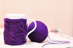 White cup with violet knitted sweater on it with ball of yarn. White mug with violet knitted thing on it and ball of yarn Stock Photo