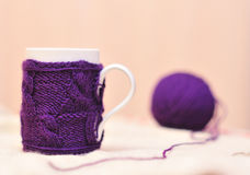 White cup with violet knitted thing on. White mug with violet knitted sweater on it and ball og yarn background Stock Photography