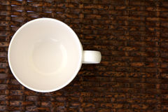 White cup on weave wood table Royalty Free Stock Images