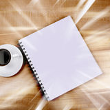 White cup and white page. On wooden table Royalty Free Stock Photos