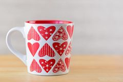White cup on wooden background. Mug with heart shape patterns Royalty Free Stock Images