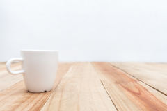 White cup on wooden table and cement wall background,Soft focus Royalty Free Stock Photos