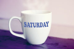 White cup with the word Saturday on it. On purple wooden table royalty free stock photo