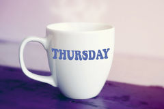 White cup with the word Thursday on it. On purple wooden table Royalty Free Stock Photography