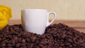 White cup and yellow flower on coffee beans. A small white mug in coffee beans. Yellow tulip on coffee beans. stock footage
