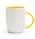 White cup with a yellow handle Stock Photos