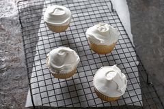 White Cupcakes on a cooling rack Royalty Free Stock Photo