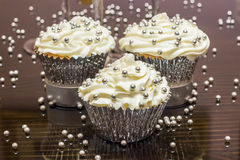 White Cupcakes with Silver Decorative Sprinkles. Some white cupcakes with silver sprinkles sitting on a reflective table stock photo