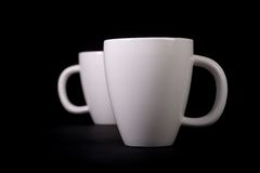 White Cups on Black Background Stock Images