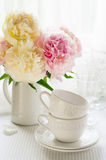 White cups and a bouquet of peonies Royalty Free Stock Images