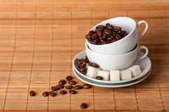 White cups and coffee grains on a saucer with sugar Royalty Free Stock Images