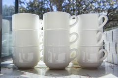 White cups for coffee piled close to window Stock Photography