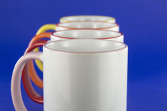 White cups with colored pens on blue background Stock Photo