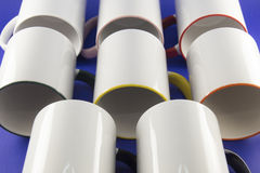 White cups with colored pens on a blue background Royalty Free Stock Photography