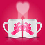 White cups with hands making heart shape. Hands making heart shape on two mugs with steam in heart shape Stock Image