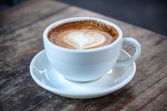 A white cups of hot coffee on vintage wooden table in cafe. Closeup image of a white cups of hot coffee on vintage wooden table in cafe stock images
