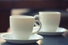 White cups on a plates on the table. Shallow depth of field Stock Images