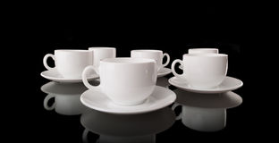 White cups and saucers on a black background Stock Images