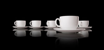 White cups and saucers on a black background Royalty Free Stock Image