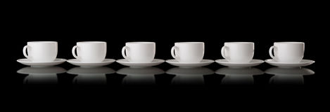 White cups and saucers on a black background Stock Image