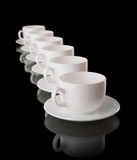 White cups and saucers on a black background Royalty Free Stock Photography