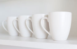 White cups on the shelf Royalty Free Stock Photos