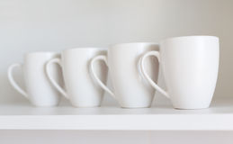 White cups on the shelf Stock Images