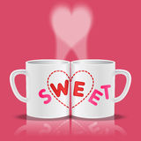 White cups with sweet word and heart shape. Sweet word and heart shape on two mugs with steam in heart shape Stock Photos
