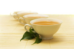 White cups of tea. Cups of tea and a green twig on the mat Royalty Free Stock Images