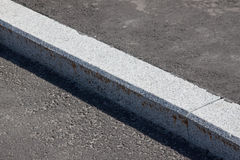 White curb and asphalt road. White curb stone border and asphalt road Stock Images