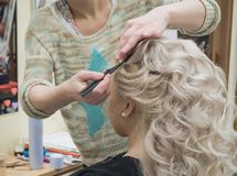 White curly curls hairstyle in the hair salon. royalty free stock image