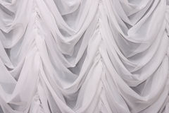 White curtain. Hanging draped white curtain. Background Royalty Free Stock Image