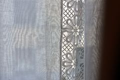 White curtain with lace close-up. White curtain with flower lace pattern in the background close-up Stock Image