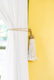 White curtain tie-back home decor simple style indoors yellow wall Stock Photo