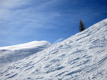 White curves on ski slopes and blue sky with clouds Royalty Free Stock Photo