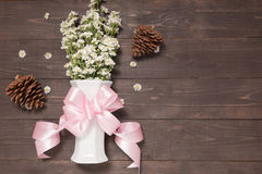 White cutter flowers are in the vase with ribbon on the wooden background and pine cones. Stock Photo