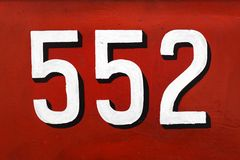 White 3d number 552 on red. White dimensional number 552 on a dark red background in a close up view Royalty Free Stock Photos