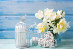 White daffodils and tulips  flowers in blue vase, candles  and d. Ecorative  heart  on turquoise  painted wooden planks against blue wall. Selective focus Stock Photo