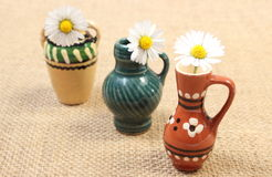 White daisies in decorative ceramic vases on jute canvas Royalty Free Stock Image