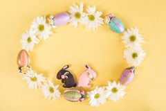 Wreath of daisies, Easter eggs, and Easter bunnies on solid pastel yellow background stock images