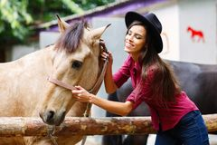 The white girl is stroking the horse and smiling. A white, dark-haired girl with a hat strokes her horse and smiles sweetly Royalty Free Stock Image