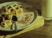White and dark waffles with fresh warm milk Close up on wooden floor.  Stock Images