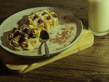 White and dark waffles with fresh warm milk top view on wooden floor.  Royalty Free Stock Photo