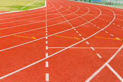 White dash line on red running track Stock Photos