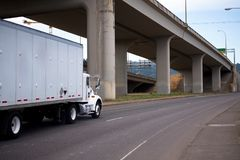 White day cab semi truck with box trailer running on the road un Stock Photography