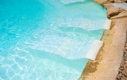 White deck chairs in the pool Royalty Free Stock Image