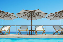 White deck chairs, umbrellas, blue sky. White deck chairs are standing under beach umbrellas near a swimming pool. A bright blue cloudless sky is above them Royalty Free Stock Image