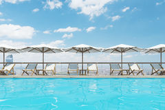 White deck chairs, umbrellas, clouds. White deck chairs are standing under beach umbrellas near a swimming pool. A blue sky with clouds is above them. 3d Royalty Free Stock Images