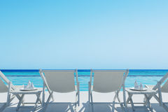 White deckchairs and a table, rair view. Rear view of white deck chairs and two coffee tables near them. A swimming pool. Cloudless sky. 3d rendering mock up Stock Photos