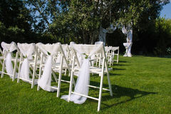 White decorated chairs on a green lawn. Arch for wedding ceremony. White decorated chairs on a green lawn. Chairs set in rows for the wedding ceremony. They are Royalty Free Stock Photos